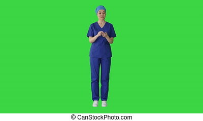Female doctor in blue uniform talking about medical care on a Green Screen, Chroma Key.