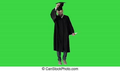Wide shot. Front view. Graduate student walking and tossing up his hat on a Green Screen, Chroma Key. Professional shot in 4K resolution. 044. You can use it e.g. in your medical, commercial video, business, presentation, broadcast