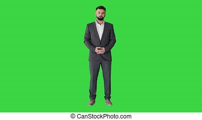 Wide shot. Front view. Handsome businessman with beard applauding on a Green Screen, Chroma Key. Professional shot in 4K resolution. 044. You can use it e.g. in your medical, commercial video, business, presentation, broadcast