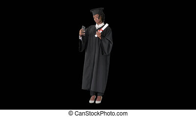 Wide shot. Front view. Happy African American female graduate holding diploma and making selfie, Alpha Channel. Professional shot in 4K resolution. 046. You can use it e.g. in your medical, commercial video, business, presentation, broadcast