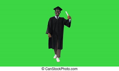 Wide shot. Front view. Happy african american male student in graduation robe walking with diploma and talking to camera on a Green Screen, Chroma Key. Professional shot in 4K resolution. 051. You can use it e.g. in your medical, commercial video, business, presentation, broadcast