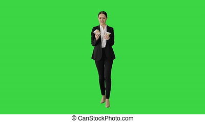 Wide shot. Front view. Happy business woman counting money while walking on a Green Screen, Chroma Key. Professional shot in 4K resolution. 043. You can use it e.g. in your medical, commercial video, business, presentation, broadcast