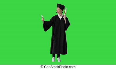 Wide shot. Front view. Happy female graduate holding diploma and making selfie on her phone on a Green Screen, Chroma Key. Professional shot in 4K resolution. 043. You can use it e.g. in your medical, commercial video, business, presentation, broadcast