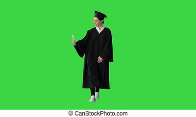 Wide shot. Front view. Happy female graduate in mortarboard making selfie on her phone on a Green Screen, Chroma Key. Professional shot in 4K resolution. 043. You can use it e.g. in your medical, commercial video, business, presentation, broadcast