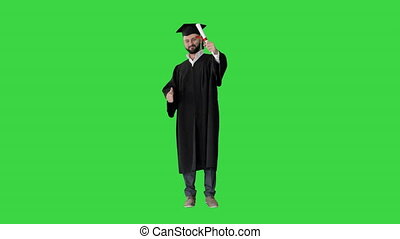 Wide shot. Front view. Happy student wearing the graduation robe and holding his certificate and raising his thumb up on a Green Screen, Chroma Key. Professional shot in 4K resolution. 044. You can use it e.g. in your medical, commercial video, business, presentation, broadcast