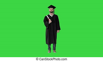 Wide shot. Front view. Happy young man in graduation hat holding diploma and talking on a Green Screen, Chroma Key. Professional shot in 4K resolution. 044. You can use it e.g. in your medical, commercial video, business, presentation, broadcast