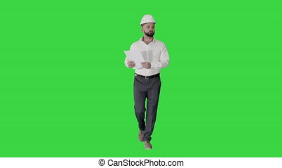 Male site contractor engineer with hard hat walking, looking...