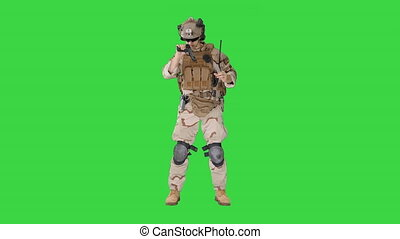 Wide shot. Front view. Marine in military uniform checking revolver gun on a Green Screen, Chroma Key. Professional shot in 4K resolution. 048. You can use it e.g. in your medical, commercial video, business, presentation, broadcast