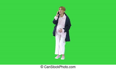 Wide shot. Front view. Pregnant woman with contractions feeling pain calling ambulance with cell phone on a Green Screen, Chroma Key. Professional shot in 4K resolution. 050. You can use it e.g. in your medical, commercial video, business, presentation, broadcast
