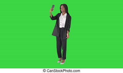 Wide shot. Front view. Pretty african amerivan female making selfie on her phone on a Green Screen, Chroma Key. Professional shot in 4K resolution. 046. You can use it e.g. in your medical, commercial video, business, presentation, broadcast