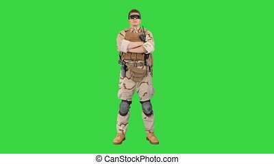 Private military contractor with crossed arms on a Green Screen, Chroma Key.