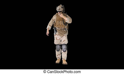 Wide shot. Front view. Ranger walks, holds a radio station and gives orders, Alpha Channel. Professional shot in 4K resolution. 048. You can use it e.g. in your medical, commercial video, business, presentation, broadcast