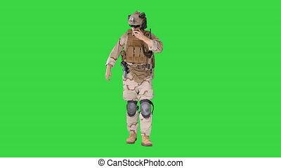 Wide shot. Front view. Ranger walks, holds a radio station and gives orders on a Green Screen, Chroma Key. Professional shot in 4K resolution. 048. You can use it e.g. in your medical, commercial video, business, presentation, broadcast
