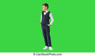 Wide shot. Front view. Schoolboy in waistcoat and bow tie checking his watch, rolling eyes and sighing on a Green Screen, Chroma Key. Professional shot in 4K resolution. 060. You can use it e.g. in your medical, commercial video, business, presentation, broadcast