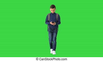 Wide shot. Front view. Schoolboy with a backpack using mobile phone while walking on a Green Screen, Chroma Key. Professional shot in 4K resolution. 060. You can use it e.g. in your medical, commercial video, business, presentation, broadcast