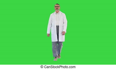 Wide shot. Front view. Senior doctor with a beard walking forward on a Green Screen, Chroma Key. Professional shot in 4K resolution. 059. You can use it e.g. in your medical, commercial video, business, presentation, broadcast