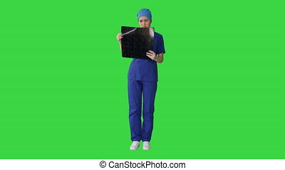 Wide shot. Front view. Serious female doctor looking at MRI scan of brain on a Green Screen, Chroma Key. Professional shot in 4K resolution. 043. You can use it e.g. in your medical, commercial video, business, presentation, broadcast