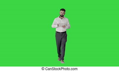 Serious young male executive using digital tablet and looking to camera agreeing on a Green Screen, Chroma Key.