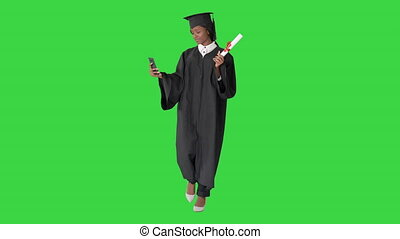 Wide shot. Front view. Smiling African American female graduate making selfie with diploma on a Green Screen, Chroma Key. Professional shot in 4K resolution. 046. You can use it e.g. in your medical, commercial video, business, presentation, broadcast