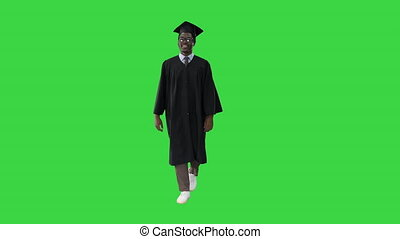 Wide shot. Front view. Smiling African American Male Student in graduation robe walking on a Green Screen, Chroma Key. Professional shot in 4K resolution. 051. You can use it e.g. in your medical, commercial video, business, presentation, broadcast