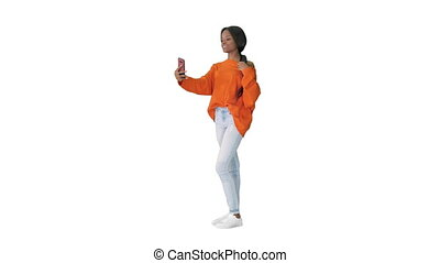 Wide shot. Front view. Smiling african american woman in bright jumper taking selfie and checking her phone on white background. Professional shot in 4K resolution. 046. You can use it e.g. in your medical, commercial video, business, presentation, broadcast