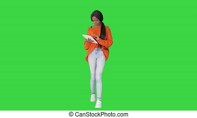 Smiling african american woman using tablet pc while walking on a Green Screen, Chroma Key.