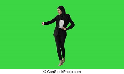 Wide shot. Front view. Smiling Arab woman in hijab taking selfies on her mobile phone as she walks on a Green Screen, Chroma Key. Professional shot in 4K resolution. 043. You can use it e.g. in your medical, commercial video, business, presentation, broadcast