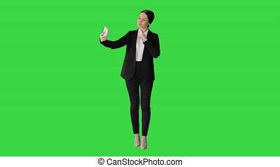 Wide shot. Front view. Smiling Businesswoman taking selfie on her phone on a Green Screen, Chroma Key. Professional shot in 4K resolution. 043. You can use it e.g. in your medical, commercial video, business, presentation, broadcast