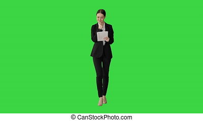 Wide shot. Front view. Smiling Businesswoman using computer pad while walking towards the camera on a Green Screen, Chroma Key. Professional shot in 4K resolution. 043. You can use it e.g. in your medical, commercial video, business, presentation, broadcast