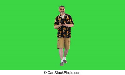 Wide shot. Front view. Smiling traveler tourist elderly gray-haired man shooting on mobile phone while walking on a Green Screen, Chroma Key. Professional shot in 4K resolution. 059. You can use it e.g. in your medical, commercial video, business, presentation, broadcast