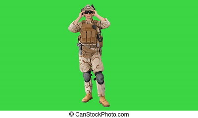 Wide shot. Front view. Soldier preparing tactical gear for action battle on a Green Screen, Chroma Key. Professional shot in 4K resolution. 048. You can use it e.g. in your medical, commercial video, business, presentation, broadcast