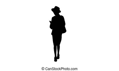 Wide shot. Front view. Stylish african american woman in knitwear and hat using her phone while walking, Alpha Channel Professional shot in 4K resolution. 046. You can use it e.g. in your medical, commercial video, business, presentation, broadcast