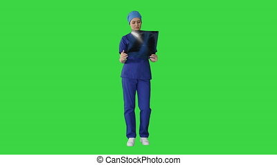 Thinking female doctor in uniform examining a chest xray on a Green Screen, Chroma Key.