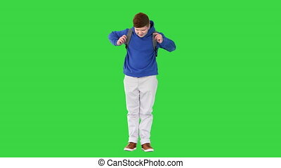 Wide shot. Front view. Young student with backpack standing on a Green Screen, Chroma Key. Professional shot in 4K resolution. 062. You can use it e.g. in your medical, commercial video, business, presentation, broadcast