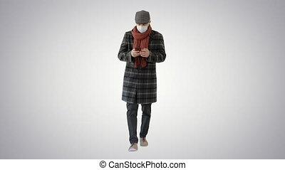 Gentleman in medical mask using phone and walking on gradient background.