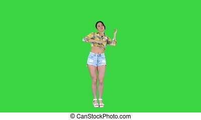Girl in square shirt and jeans shorts, sneakers, dancing on...