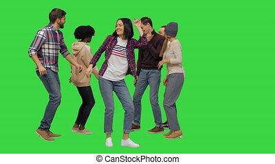 Group of happy young people dancing together on a Green Screen, Chroma Key.