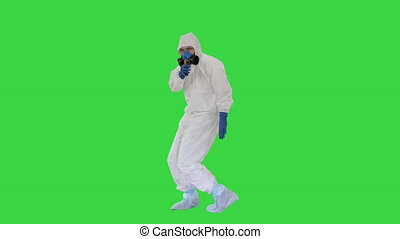 Wide shot. James Bond parody Doctor wearing gloves with biohazard chemical protective suit checking temperature on a Green Screen, Chroma Key. Professional shot in 4K resolution. 53. You can use it e.g. in your medical, commercial video, business, presentation, broadcast