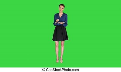 Lady with short hair wearing formal clothes holding a tablet in her hands and talking to camera on a Green Screen, Chroma Key.