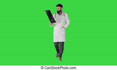 Wide shot. Male turk physician walking and reviewing a MRI brain scan on a Green Screen, Chroma Key. Professional shot in 4K resolution. 4151. You can use it e.g. in your commercial video, business, presentation, broadcast