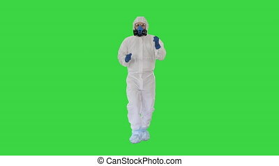 Wide shot. Man in hazamat suit walking and dancing Covid-19 concept on a Green Screen, Chroma Key. Professional shot in 4K resolution. 53. You can use it e.g. in your medical, commercial video, business, presentation, broadcast