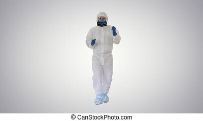 Wide shot. Man in hazamat suit walking and dancing Covid-19 concept on gradient background. Professional shot in 4K resolution. 53. You can use it e.g. in your medical, commercial video, business, presentation, broadcast