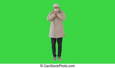 Man in top clothes and in medical disposable mask coughing on a Green Screen, Chroma Key.