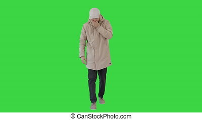 Wide shot. Man in winter outfit walking and coughing on a Green Screen, Chroma Key. Professional shot in 4K resolution. 53. You can use it e.g. in your medical, commercial video, business, presentation, broadcast