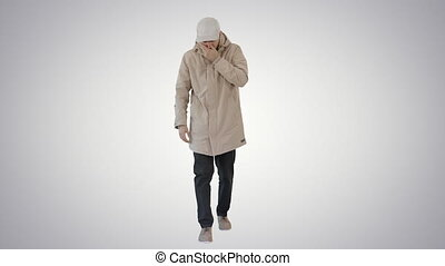 Wide shot. Man in winter outfit walking and coughing on gradient background. Professional shot in 4K resolution. 53. You can use it e.g. in your medical, commercial video, business, presentation, broadcast