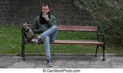 Man smoking while sitting on bench outdoors.
