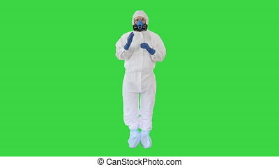 Wide shot. Man Wearing HAZMAT Protective Clothing Showing That He Wears Gloves on a Green Screen, Chroma Key. Professional shot in 4K resolution. 53. You can use it e.g. in your medical, commercial video, business, presentation, broadcast