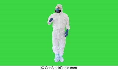 Wide shot. Medical doctor in hazamat clothes pointing on imaginary screen on a Green Screen, Chroma Key. Professional shot in 4K resolution. 53. You can use it e.g. in your medical, commercial video, business, presentation, broadcast