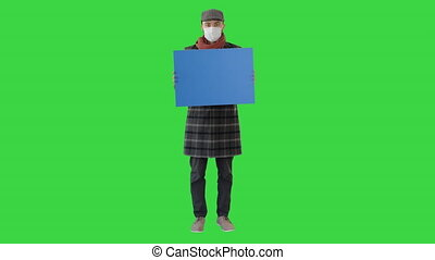 Wide shot. Mockup blue screen. Man in a trendy outfit and medical mask holding blank placard on a Green Screen, Chroma Key. Professional shot in 4K resolution. 53. You can use it e.g. in your medical, commercial video, business, presentation, broadcast