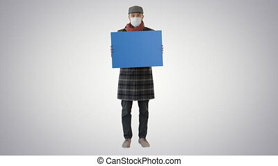 Wide shot. Mockup blue screen. Man in a trendy outfit and medical mask holding blank placard on gradient background. Professional shot in 4K resolution. 53. You can use it e.g. in your medical, commercial video, business, presentation, broadcast